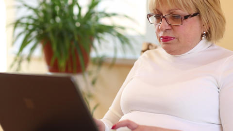 Senior woman types text using laptop. Woman with notebook Footage