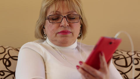 Blonde woman with red smartphone sits on the sofa and listens to music Footage
