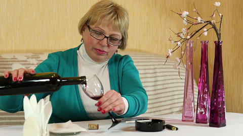 Woman pours and drinks red wine Footage