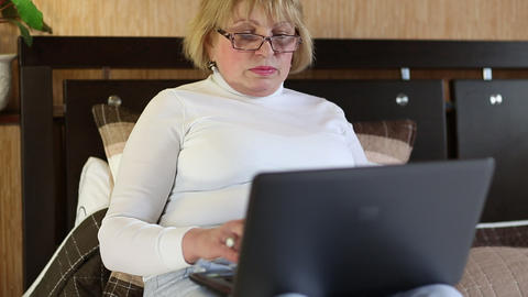 Senior woman types text using laptop Footage