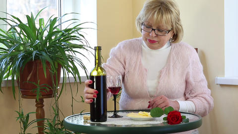 Woman sits at a table pours and drinks red wine Footage