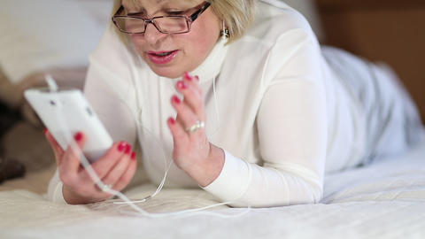 Senior woman with white smartphone lies on the bed Footage