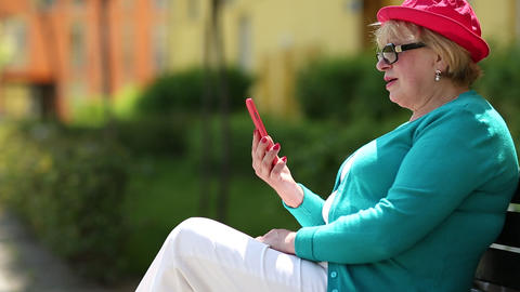 Woman in red cap sits on the bench and communicates via red smartphone Footage