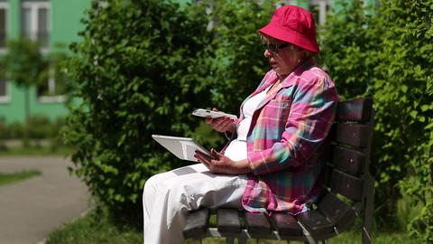 Woman with Tablet-PC sits on the bench and talks on the cell phone Footage
