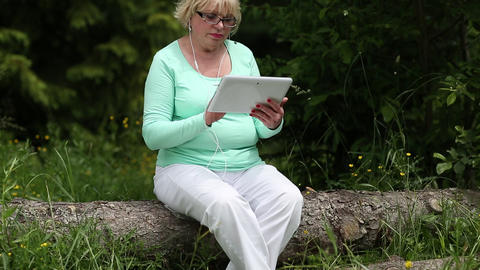 Woman sits on a fallen tree in the forest and uses Tablet PC Footage