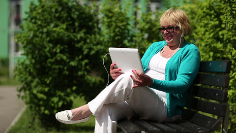 Blonde woman sits on the bench and communicates via Tablet-PC Footage