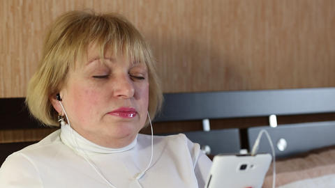 Blonde woman with closed eyes sits on the sofa and listens to music Footage