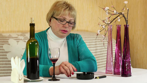 Woman drinks wine and smokes a cigarette Footage