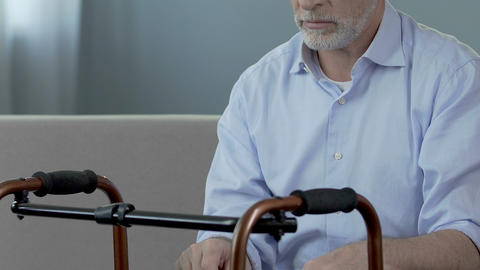 Old man sitting and looking at walking frame, spine trauma, indecisiveness Footage