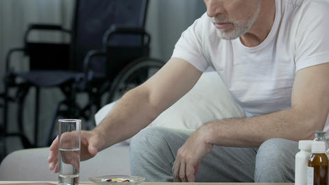 Elderly male taking pill, looking at wheelchair standing at background, trauma Footage
