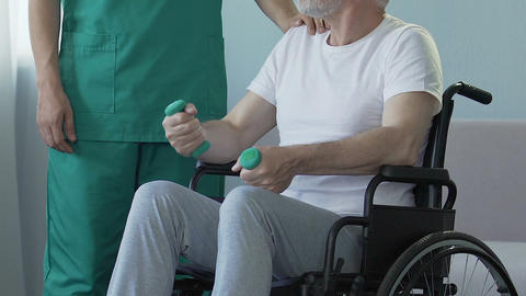 Aged man sitting in wheelchair, holding dumbbells, talking to nurse, recovery Footage