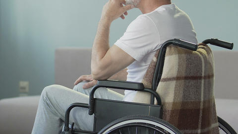 Aged man sitting in wheelchair looking at legs and nodding, lost ability to walk Footage
