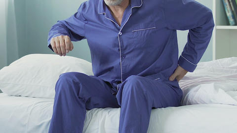 Elderly man sitting on bed edge, stretching and having sudden lower back pain Footage