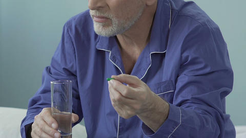 Aged male holding pill in one hand, glass of water in another, sighing heavily Footage
