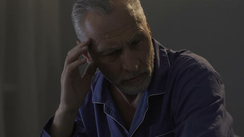 Elderly male sitting on bed in dark room, rubbing his temples, strong headache Footage
