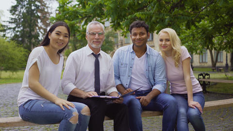 Happy teacher and multi-ethnic students sitting on bench, smiling into camera Footage