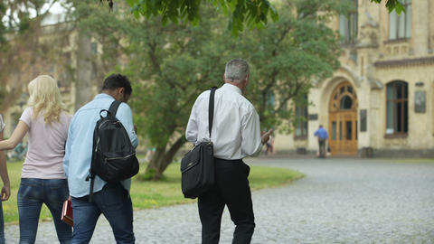 Multiracial students walking with their dean to academy, chatting about thesis Footage