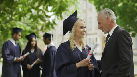 Excited dad congratulating graduate daughter in park near academy, happiness Footage