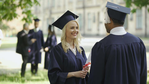 Graduate female student talking to male graduate, touching hat, happy friends Footage