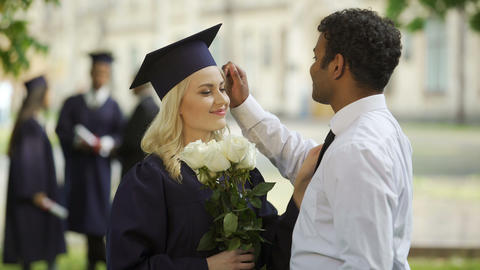 Female graduate in academic regalia with flowers talking to boyfriend, education Live Action