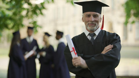 Senior man in academic regalia holding diploma, education at any age, new degree Live Action