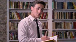 Young businessman is reading book in library, watching at camera, relax concept Footage