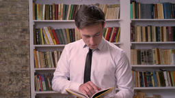 Young businessman is searching information in book in library, watching at Footage