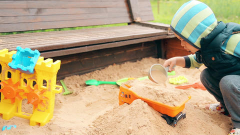 A little boy in kindergarten playing in the sandbox with sand Footage