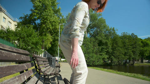 Woman in white casual clothes with red hair sits on the bench near the pond Footage