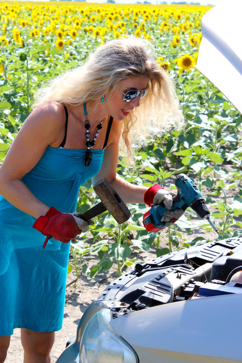 Blonde with tools about open bonnet. Funny blonde trying to repair the machine フォト