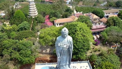 huge grey Buddha statue against pagoda and blue sky Footage