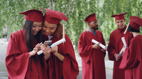 Attractive young women happy graduates are watching photos on smart phone and Footage