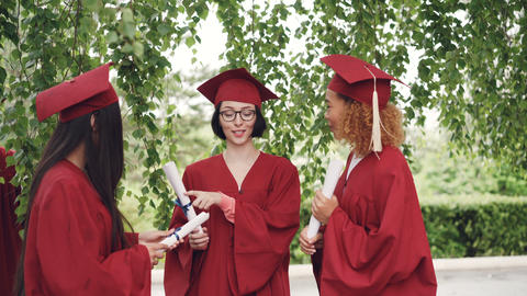 Three pretty girls graduates are talking and holding diplomas on graduation day Footage