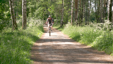 A man is riding a bicycle on a forest path. He leads a healthy lifestyle Live Action