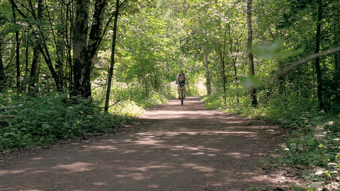 A man is training in the park. He rides a bicycle on a summer day, on special Footage