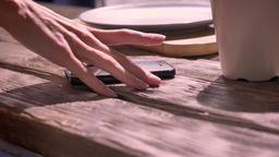 Sexy woman's hand taking phone from wooden table, smartphone lying on table with Footage