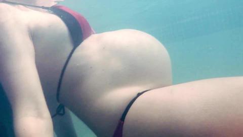 Young pregnant woman in bikini swimming in pool ビデオ