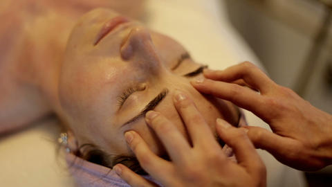 Face Massage in beauty spa salon. Female enjoying relaxing face massage in Footage