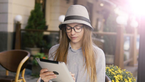 Girl Uses Tablet in Outdoor Cafe Live Action
