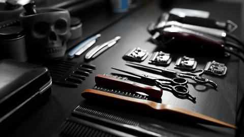 Stylish equipment table with scissors and trimmers and dark scull at the barber Footage