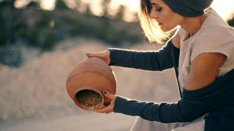 girl in ethnic dress sits near the road and pours sand out of the pitcher. The Live Action