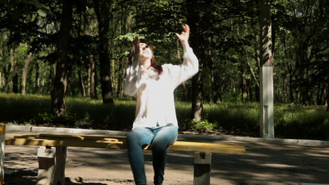 Girl throws the book high and with great difficulty catches it Footage