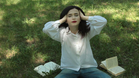 Tired from reading the book, the girl relaxes Footage