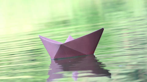 Three colored paper boats floating on water Footage
