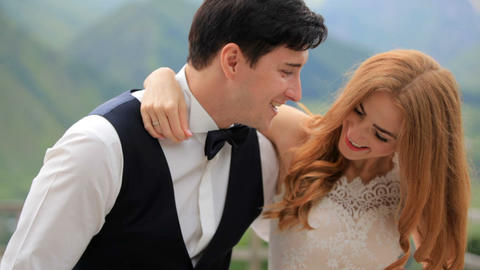 Merry groom and bride against the backdrop of high mountains. The bridegroom is Live Action