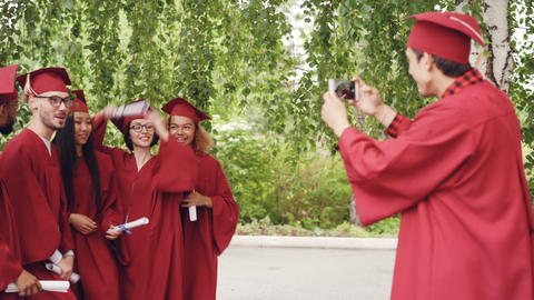 Young man with smartphone is taking pictures of graduates having fun posing with Footage