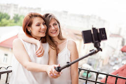 Happy and positive female friends taking a selfie フォト