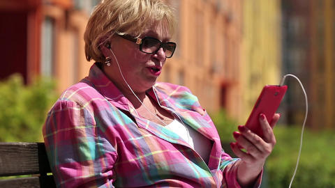 Blonde woman sits on the bench and communicates via smartphone Footage