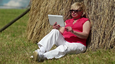 Blonde woman sits on a green grass near haystack and uses tablet PC Footage