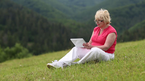 Blonde woman sits on green grass and uses tablet computer Footage